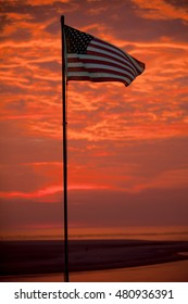 """US Flag with dramatic """"Fire Sky"""" sunrise in the background"""