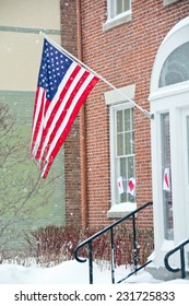 A US flag flies outside an office building with heavy snow falling.