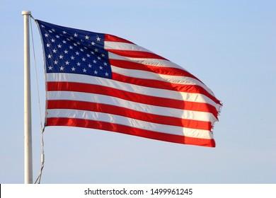 US Flag flying on a staff on light blue background