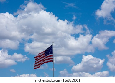 US Flag flying in the wind with clouds and a blue sky on a sunny day