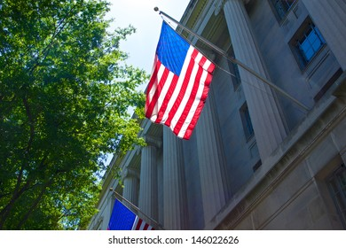 US flag hangs from the columns on the Department of Justice.