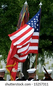 US flag and honor guard with gravestones in background Arlington National Cemetery