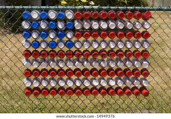 A US flag made of plastic cups in a chain link fence.