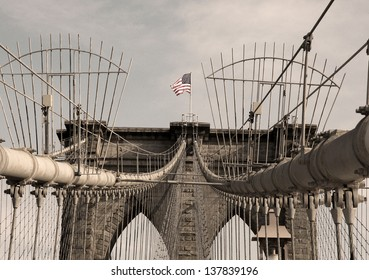 US flag on Brooklyn Bridge, New York City - sepia toned image.