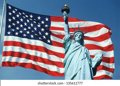 US flag on a flagpole waving in the wind set against a blue sky with Statue of Liberty