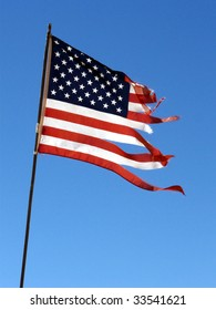 US flag in shreds blowing in the strong wind