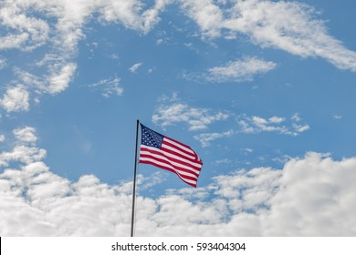 US flag surrounded by blue sky and cumulus clouds. Copy space.