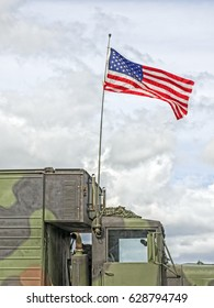 US flag waves at a military vehicle