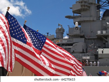 US flags flying beside the Battleship Missouri in Pearl Harbor, Honolulu, Oahu, Hawaii with 4 sailors walking on deck.