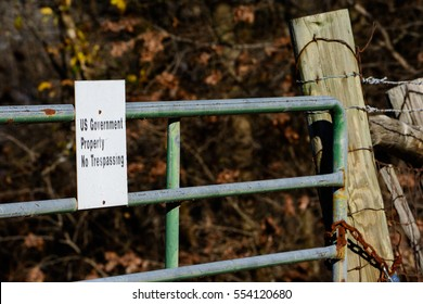 US Government Property sign on locked gate with thick woods in background close crop. Illustrates government land, control, eminent domain laws and land grabs