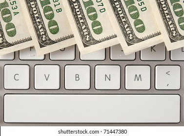 US hundred dollar bills on white computer keyboard with spacebar.