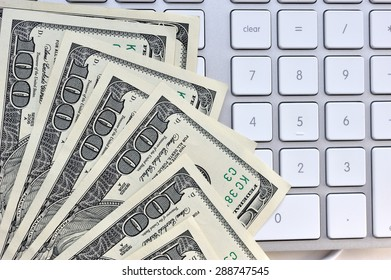 US hundred dollar bills with white modern computer keyboard isolated on white background, selective focus.