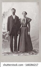 US - ILLINOIS - CIRCA 1897 - A vintage Cabinet Card  photo of a young couple. They are both standing. The woman is dressed in a Victorian style dress. A photo from the Victorian era. CIRCA 1897