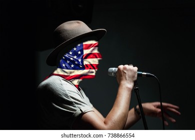 US Independence Day. The concept: propaganda of the American way of life, patriotism. The person speaks into the microphone, the US flag blocks the person's face.