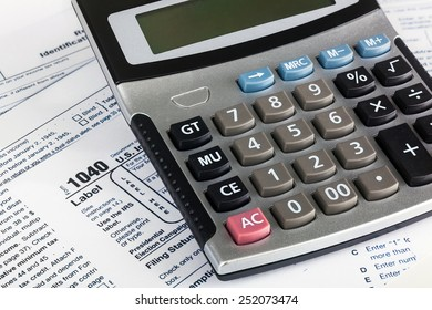 US Individual Tax Return Form 1040 close up with calculator.