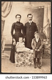 US - KANSAS - CIRCA 1885 - A vintage photo of a family of four. The mother and father are standing behind their son and baby daughter. A photo is from the Victorian era. CIRCA 1885