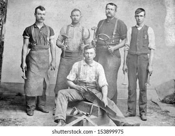 US - KANSAS - CIRCA 1885 - A vintage photo of a group of four young blacksmith's and one carpenter. They are holding the tools used by blacksmiths and carpenters. Photo from Victorian era. CIRCA 1885