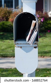 US Mail box with newspaper and letters in front of a house
