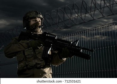U.S. marine soldiers patrol the area. Military against the fence with barbed wire. Border Wall.