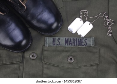 U.S. MARINES Tape with dog tags and boots on olive green uniform background
