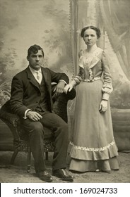 US - MASSACHUSETTS - CIRCA 1890 - A vintage antique photo of a young couple. The husband is sitting while his wife is standing behind the chair. A photo is from the Victorian era. CIRCA 1890
