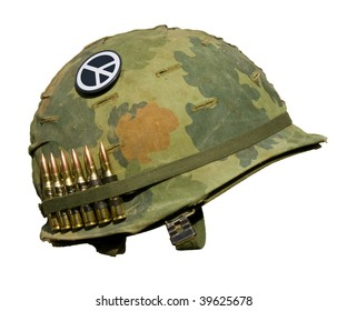 A US military helmet with an M1 Mitchell pattern camouflage cover from the Vietnam war, with six rounds of 7.62mm ammunition and a peace symbol button.
