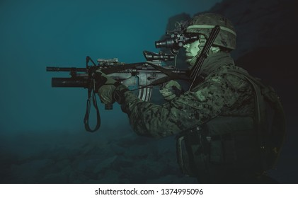 US military marine in the night with a night vision device