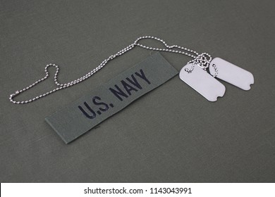 U.S. Navy Branch Tape with dog tags on olive green uniform background