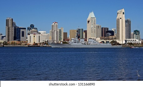 US Navy ship sails in front of the skyline of San Diego, California