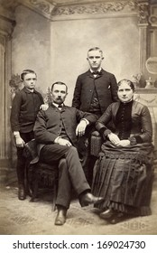 US -NEW YORK - CIRCA 1880 - A vintage antique photo of a family of four. The mother and father are sitting with their sons standing behind them. A photo is from the Victorian era. CIRCA 1880