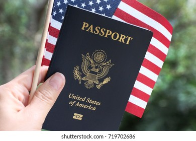 US passport and American flag as background, hand holding passport and flag