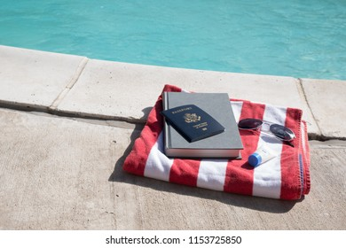 US passport, novel, sunglasses, and travel size bottle of sunscreen sitting on a red and white striped beach towel next to a swimming pool.  Pool still life, getting ready to go on vacation.