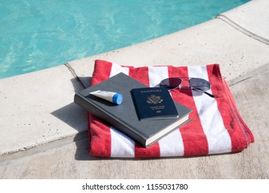 US passport, sunglasses, sunscreen  and a hardcover novel on the side of the pool on a red a white striped beach towel. Getting ready for vacation. Pool still life. Book and sunscreen next to pool.