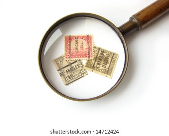US postage stamps and magnifying glass on white background