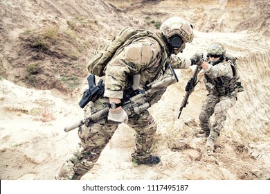 US ranger, modern infantryman, special reconnaissance team member or military scout in ammunition, armed with service rifle helping brother in arms to climb on sand dune. Army brotherhood and teamwork
