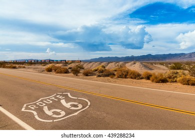 U.S. Route 66 highway, with sign on asphalt and a long train in the background, near amboy, california. Located in the mojave dessert