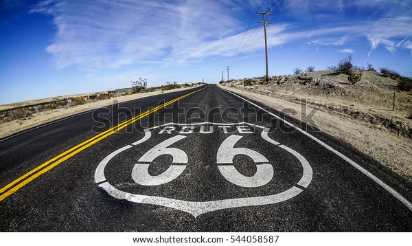 U.S. Route 66 highway, with sign on asphalt. Located in the mojave dessert