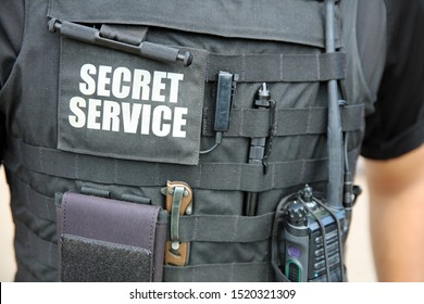 U.S. Secret Service officer, wearing a vest with various equipment attached, stands in front of White House. Washington DC. USA