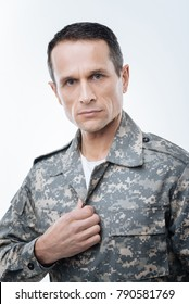 US serviceman. Nice handsome smart man wearing a uniform and looking at you while doing military service