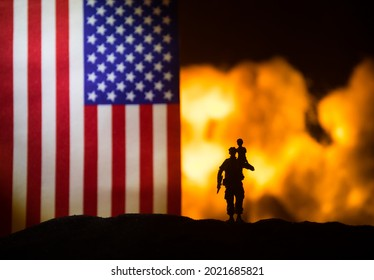 US small flag on burning dark background. Concept of crisis of war and political conflicts between nations. Silhouette of armed soldier against a USA flag. Selective focus