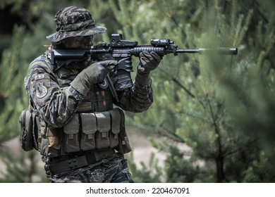 US soldier aiming with assault rifle at target