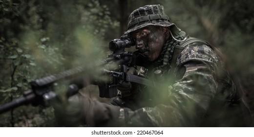 U.S. soldier dressed in tiger stripe camouflage, hidden in jungle