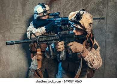 US special operations forces fighters armed with assault rifle, in opscore helmet. Studio shot