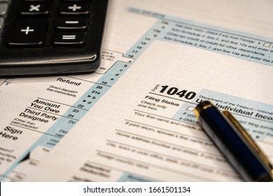 US tax form 1040 with pen and calculator. background