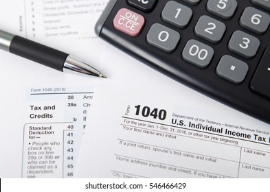 US tax form 1040 with pen and calculator. tax form law document usa white mathematics business concept