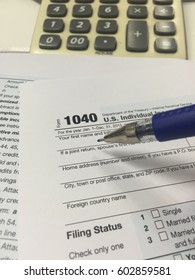 US tax form 1040 with pen and calculator. tax form law document USA white mathematics business concept.