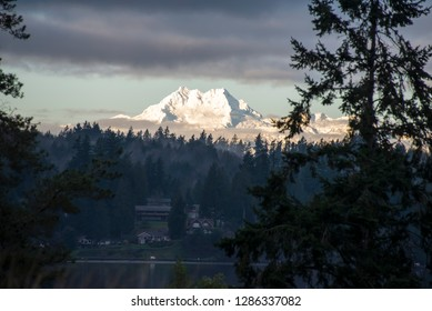 US, WA, Kitsap Peninsula. View from Bainbridge Island of Olympic Mountains and waterfront homes of Brownsville. These peaks known as 'the Brothers'.