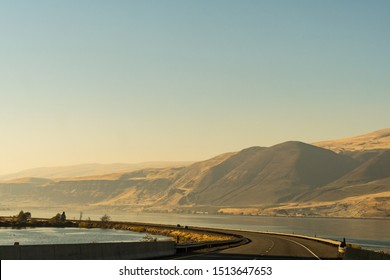 The US-30 highway passing by the Columbia River with water on both sides of the road near The Dalles, Oregon, USA.