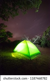 USA, Arizona, Navajo Nation, Navajo National Monument. A green glowing camping tent under the stars at the free Canyon View Campground.