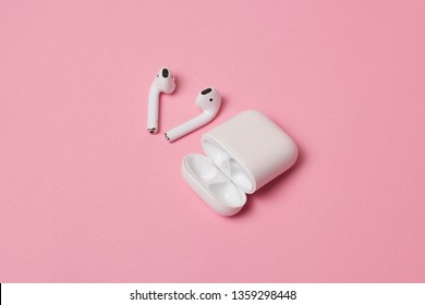 USA, California - March 2019: Airpods and Earpods are lying on a wooden surface. Two pairs of headphones from apple on a wooden table